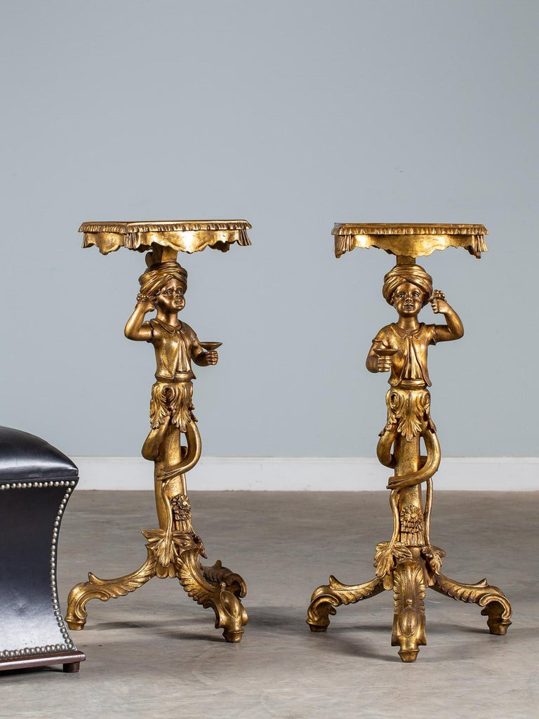 A pair of vintage Italian Venetian gilded Blackamoor pedestal column figures circa 1950 each holding aloft a cluster of grapes and a goblet. Please notice the figures are facing each other with the grapes and goblets in opposite hands. The top of