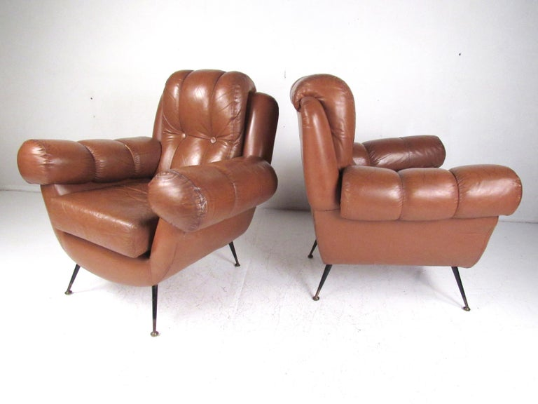 This impressive pair of vintage modern club chairs features tufted leather upholstery, tapered metal legs, and plush padded seats. Unique rounded armrests add to both comfort and Italian modern style of the pair. Please confirm item location (NY or