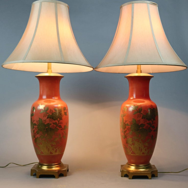 A vintage pair of Chinese double socket table lamps offer porcelain urn form base with gold gilt floral decoration, seated on gilt metal footed bases, 20th century  ***DELIVERY NOTICE – Due to COVID-19 we have employed LIMITED-TO-NO-CONTACT
