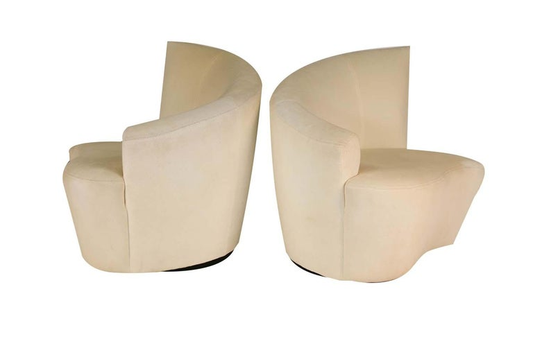 Superb pair of sculptural Bilbao swivel lounge chairs designed by Vladimir Kagan for Weiman Preview. Features beautiful and uniquely stylish shaped, curved angular backrests/armrests, with comfortable plush seats. Chairs rest on circular swivel