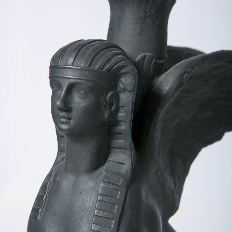 Why we love it: They are ready to soar! A pair of Wedgwood black basalt sphinxes, each modeled seated upright atop a raised rectangular base with 'lotus' nozzle to hold candles. The sphinxes have the head of a woman, the body of a lion, and a pair