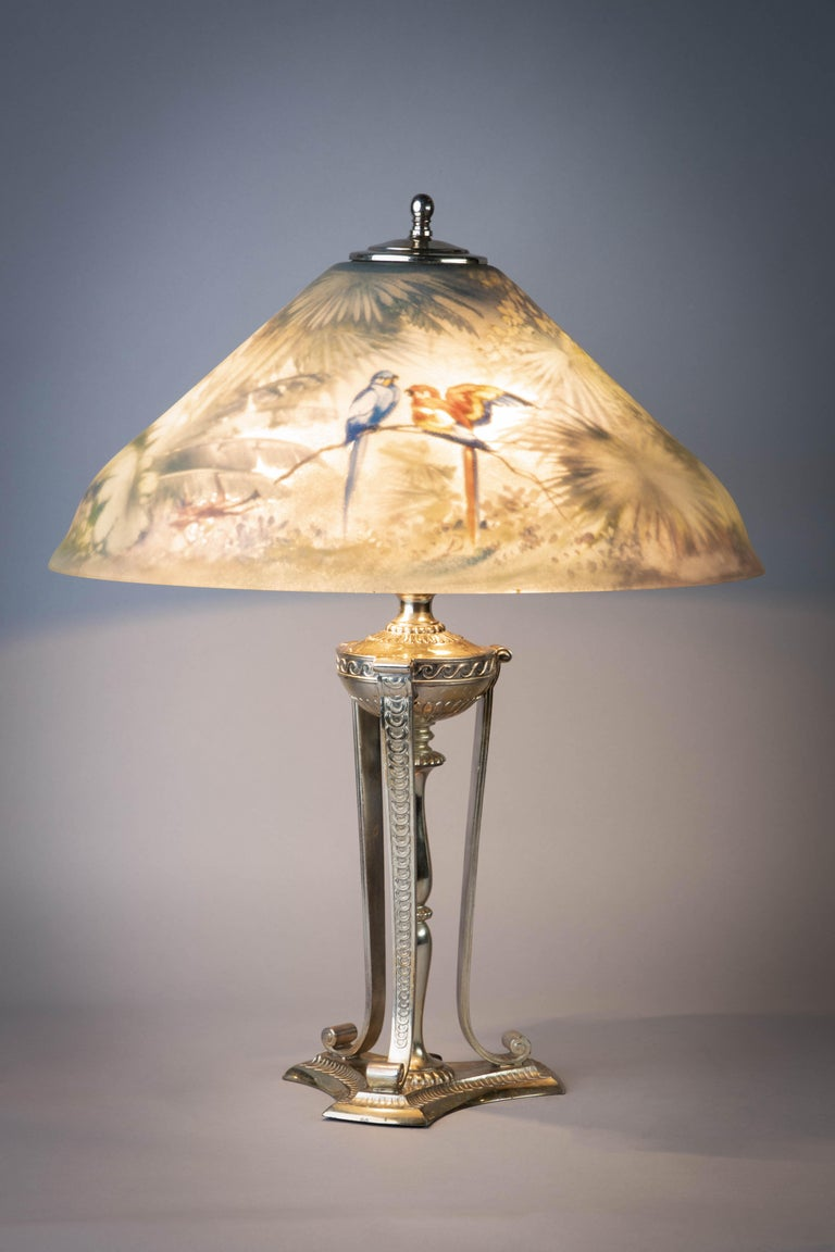 The conical shade decorated with birds perched on tropical branches, three-light socket, on a neoclassical style urn and columnar standard flanked by three pillar supports ending in scrolling feet and a stepped triangular base.