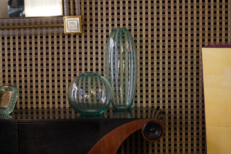 Formia luxury glass are punched, this pairs of Murano vases.  Pair of Murano vases of different shapes, but combined with one another. One of narrow and long shape, while the other is spherical. Their color is a light green and blue, but
