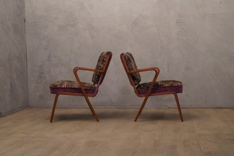 Pair of armchairs dressed in a precious violet velvet fabric with embroidery from an important Italian silk factory.  The pair of armchairs has a wooden part in light curved wood, this part runs all around the armchair, to form the structure and the