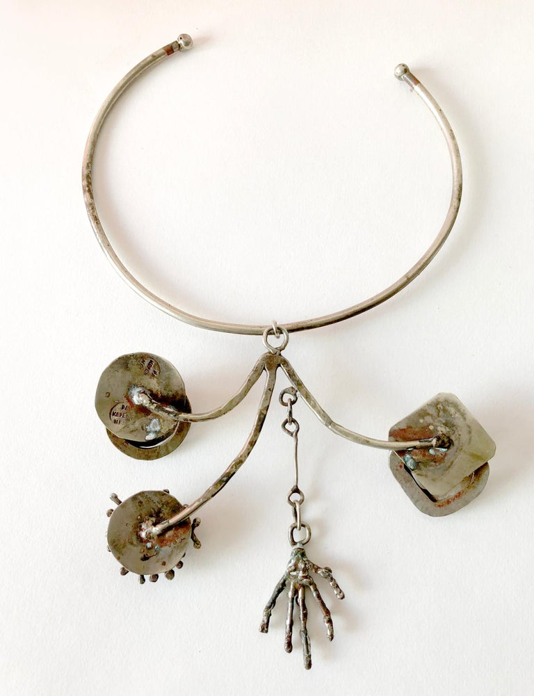 Silver plate kinetic necklace created by Pal Kepenyes of Acapulco, Mexico.  Necklace pendant consists of three arms  with spinning ends and one skeletal hand suspending from a chain at center.  Pendant measures 4.5