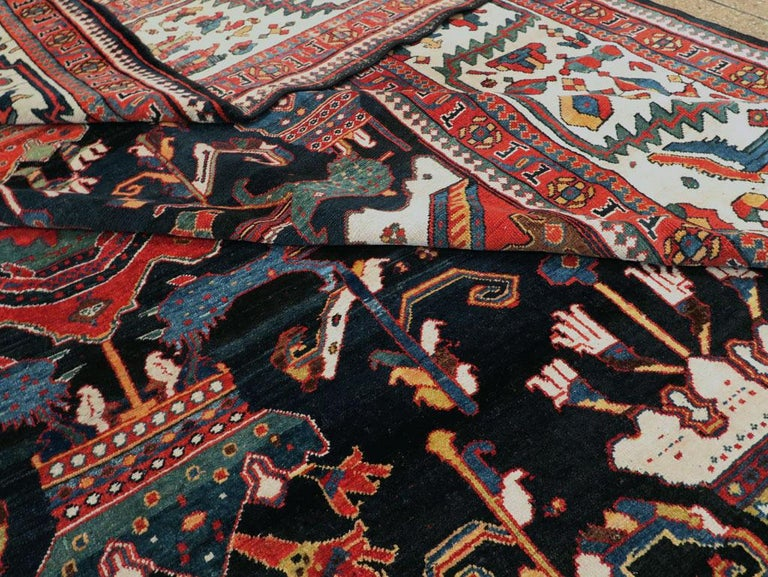 A magnificent palace size early 20th century Persian Bakhtiari rug from the early 20th century. Large scale all-over design on a dark brown and navy blue ground with lobed diamond shaped medallions with attached top and bottom royal crowns flanked