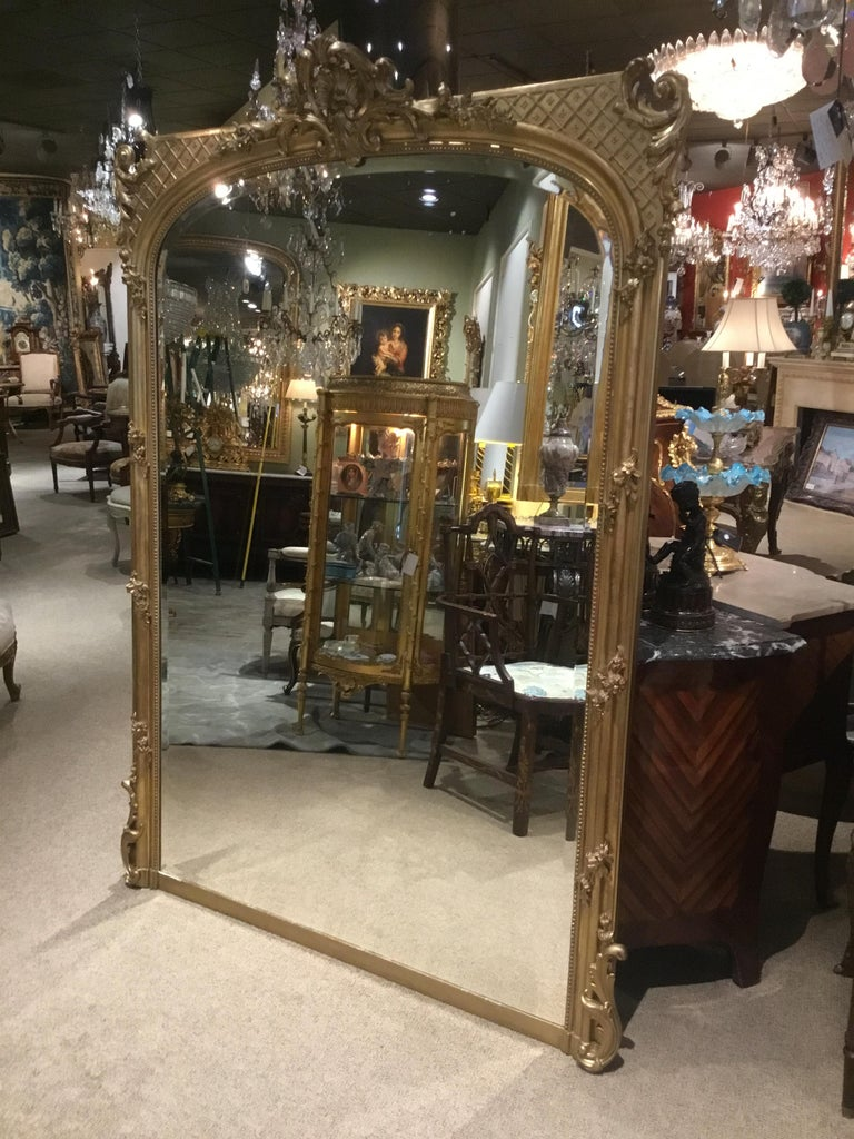 Large and beautiful Louis XV-style giltwood framed mirror with beveled plate.. Shell cartouche is centered at the crest with exquisite scrolls that surround the Cartouche. The top of the mirror is gracefully curved and the upper corners Have