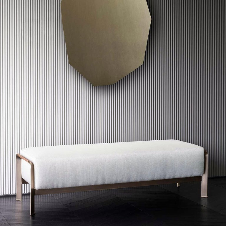 Bench Palacio with solid wood structure, upholstered and covered with white fabric, Cat B. Bench with Bronze frame and with brown leather covering on frame sides. Also available with other fabrics or leathers on request.