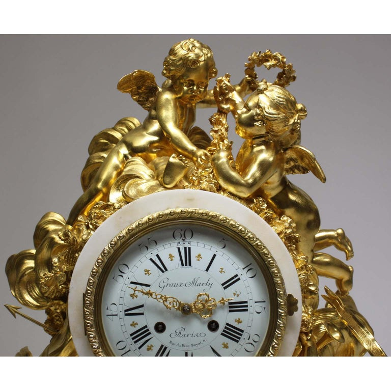 An Important and Palatial French Louis XV Style 19th Century Gilt-Bronze and White Marble Cherub Mantel Clock, attributed to Alfred-Emmanuel-Louis Beurdeley, the casting and gilding by Graux-Marly, Paris, the movement by P. Marti et Cie. The large