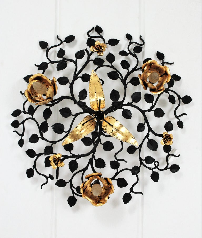 Monumental rosebush floral flush mount / wall light with roses and leaves in black and gilded wrought iron. Spain, 1940s. This hand-hammered iron bush is patinated in black color and accented by roses and leaves with gold leaf gilt finishing. The