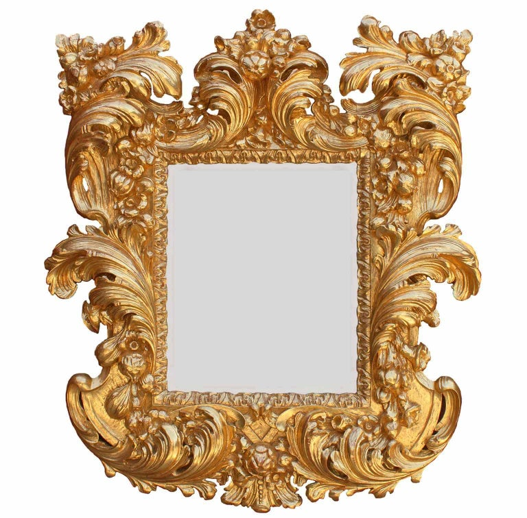 A fine Palatial Italian, 19th century baroque style vigorously carved Florentine giltwood mirror frame. The ornately carved frame with scrolls, acanthus, fruits and floral design, fitted with a later beveled mirror plate. All gilding is 24-carat
