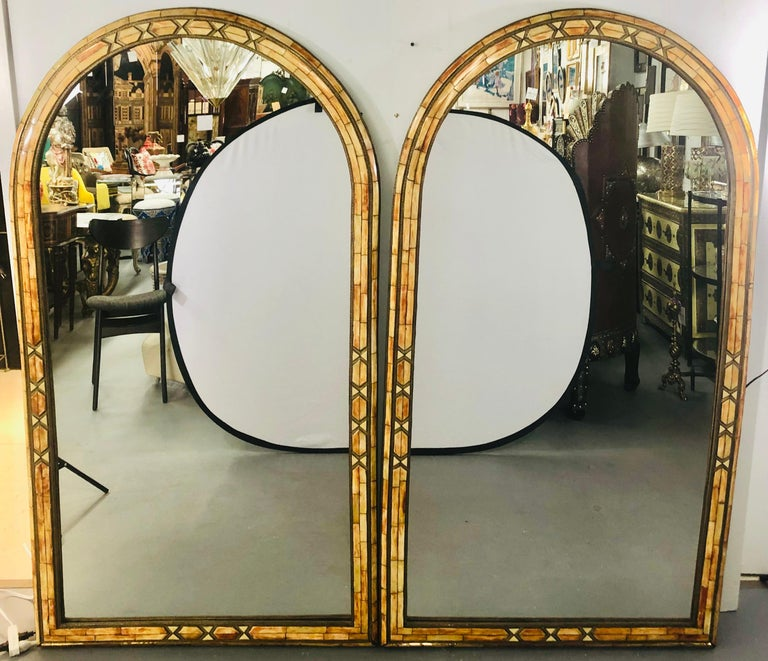 Wall console or pier mirror palatial Moroccan Hollywood Regency fashioned, pair With generous pieces of orange camel bone set into a frame of brass, these uniquely constructed mirrors exude a muted, fiery glow and warm tones. The mirrors are