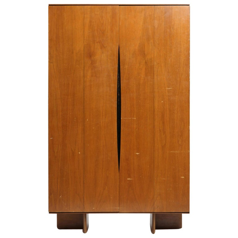 A Mid-Century Modern pale cherrywood wardrobe designed by Vladimir Kagan. This wardrobe has a rectilinear form with bi-fold doors with long distinctive Minimalist recessed pulls, the entire form resting on L-shaped legs. Made by Kagan-Dreyfuss in