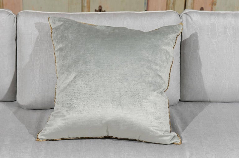 A cushion made of an antique Ottoman Empire raised gold metallic embroidery bordered with antique gold metallic gallon on pale French blue velvet. This down filled square pillow was hand trimmed with a vintage gold metallic cording knotted in the