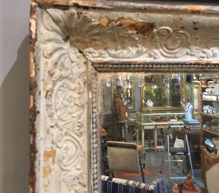 Distressed 19th century rectangular mirror from France with pale mint green / cream painted frame. Old mirror with lots of foxing and diamond dust in the mirror at corners.