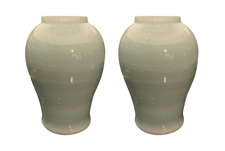 Contemporary Chinese pair of pale turquoise Classic shape ceramic lamps with cream colored Belgian linen shades. Newly wired. Measures: Overall height 29
