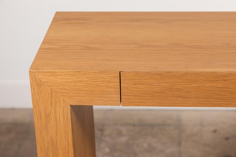 The palisades console with metal inset base is composed of a simple American walnut or white oak frame that features two drawers and rests atop a recessed metal base. Shown here in oiled oak and matte black powdercoat.   Available to order in