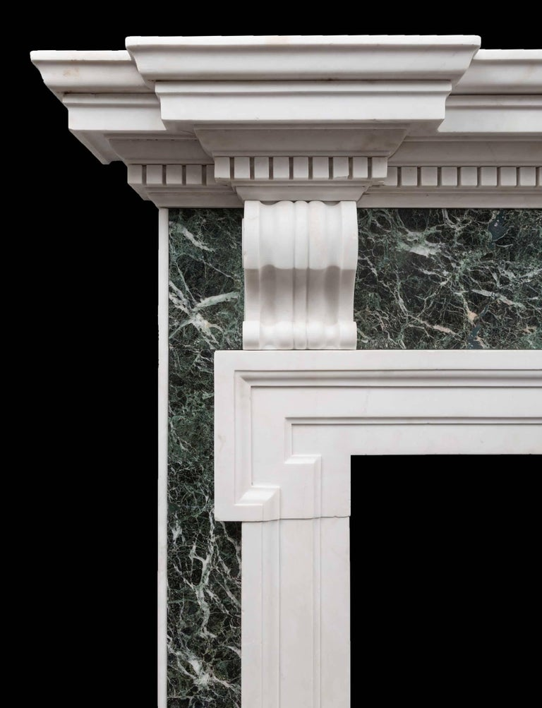 An antique green Verde Antico and white statuary Carrara marble fireplace in the Palladian style. Large in scale and wonderfully proportioned. The substantial dentil cornice rests on a Verde Antico frieze with two scrolled bracket corbels. The