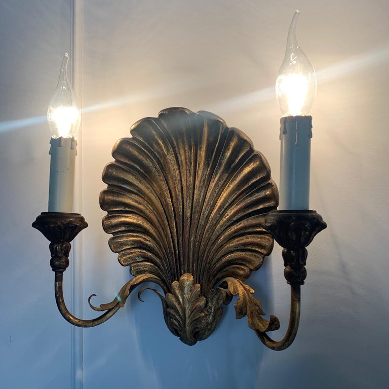 Palladio Italian shell wall lights, 1970s A pair of gilt clam shell wall sconces Metal arms with decorative metal acanthus leaf shaped details Original Palladio sticker on the back dated Nov 73 Decorative cups, each holding a single lamp holder,