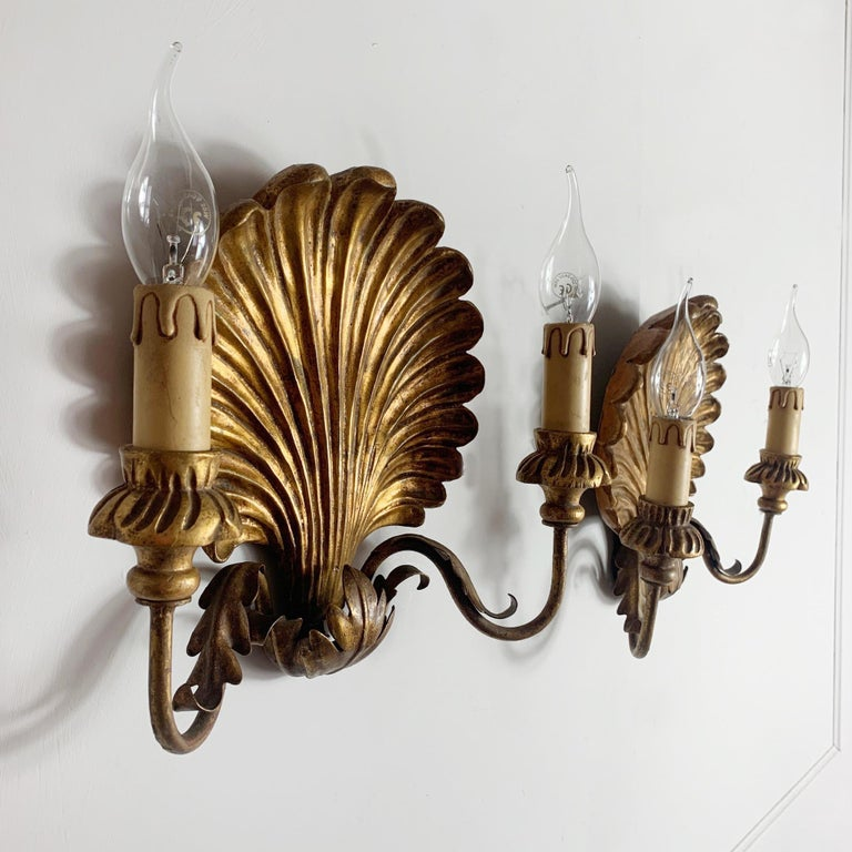 Palladio Italian shell wall lights, 1950s A pair of carved gilt wooden clam shell wall sconces Metal arms with decorative metal acanthus leaf shaped details Decorative carved wooden cups, each holding a single lamp holder, e14 bulbs Measures:
