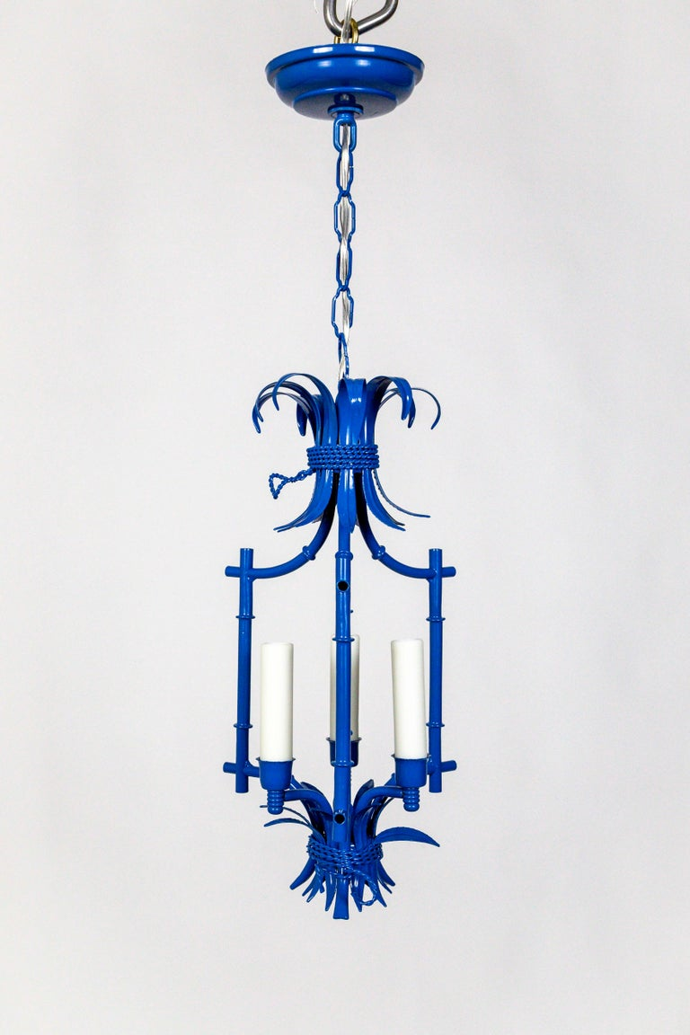 A fantastic pair of petite, blue, Mid-Century Modern, Palm Beach Style, faux bamboo lanterns. These whimsical, 3-light pendants have been refurbished to 'like-new' condition, with a fresh powder coat of blue enamel; with polyresin candle covers,