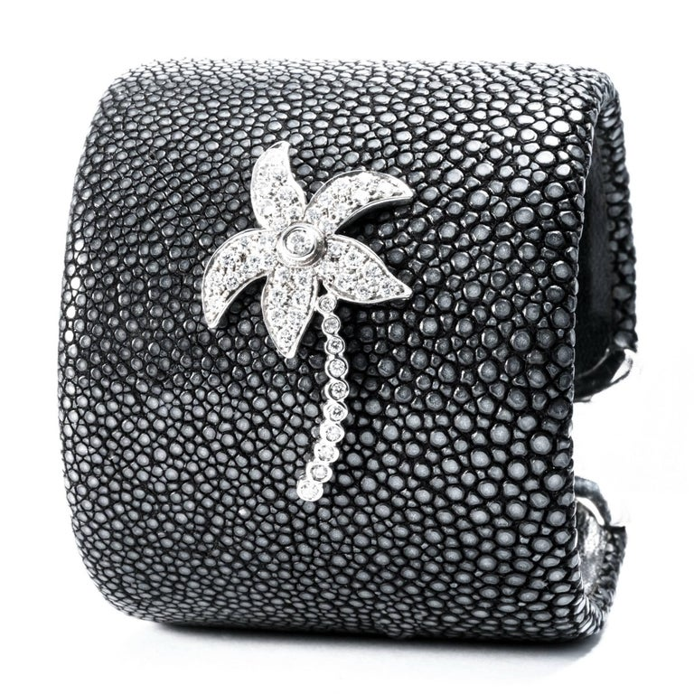 Shagreen's deep black granular surface is handcrafted  in a large c-bangle bracelet with  extra-white diamonds to design a lively palm decoration. With 1 diamond carats 0.05 and 47 diamonds carats 0.95. Set in white gold 18K  Fits wrist size up to
