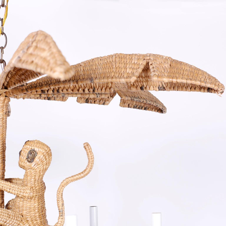 Mario Torres wicker or chuspata chandelier with a palm leaf top, climbing monkey, and six lights with copper branches divided by palm leaves.