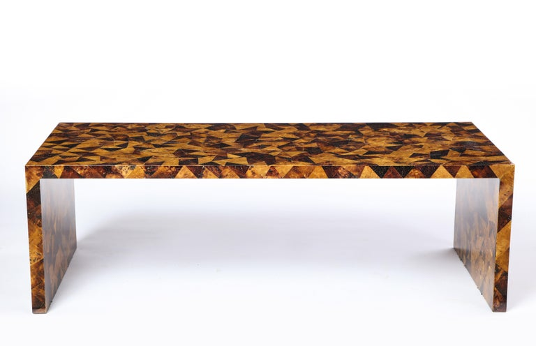 This modern art deco style palmwood low coffee table is visually stunning. The table is finished with a heavy coat of varnish, giving sleekness to the warm brown and tan tones and geometric pattern. The table's rectangular shape and waterfall sides