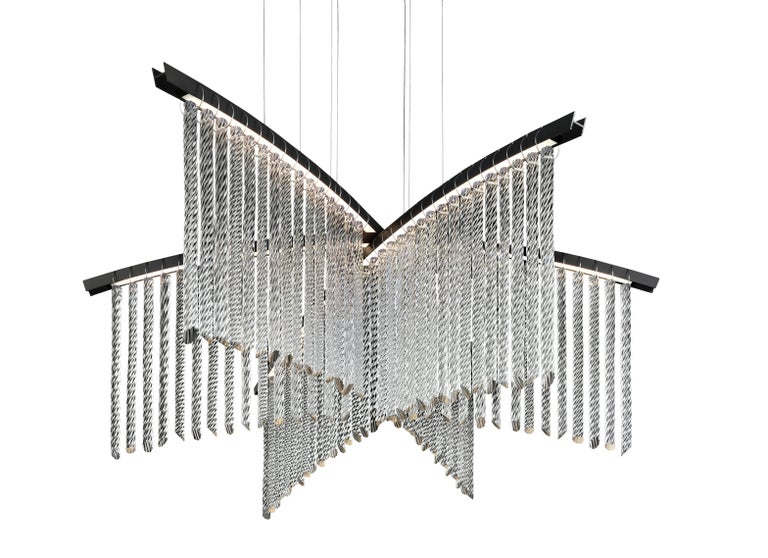 Palmyra is a very light chandelier, characterized by a sinuous line, able to embellish and illuminate any environment with its LED technology. Here you are shown the Palmyra 7274 Suspension Lamp in Crystal Glass with an Anodized Black finish and