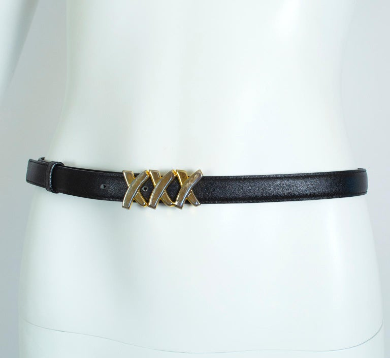 With its narrow profile, this glam Paloma Picasso belt will thread through all but the very skinniest belt loops and has just enough gold to complement your favorite Chanel 2.55 chain bag.  Black leather belt with gold hardware; tethered leather