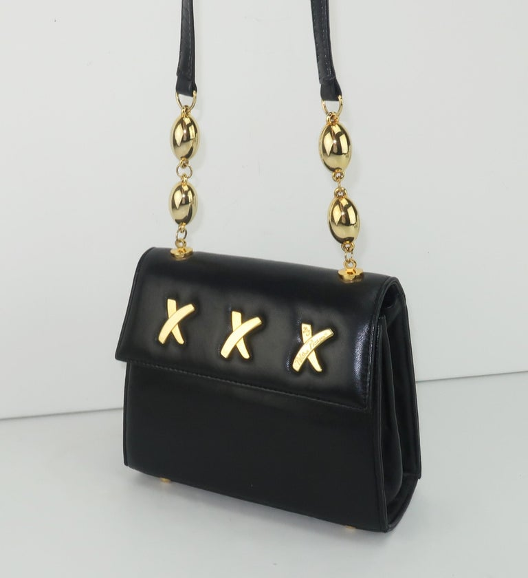 A classic Paloma Picasso shoulder strap handbag in a supple black leather with the iconic 'X' logo in gold tone metal ... triple kisses from Ms. Picasso!  The long shoulder strap is accented by gold tone spheres and one 'X' on the exterior is signed