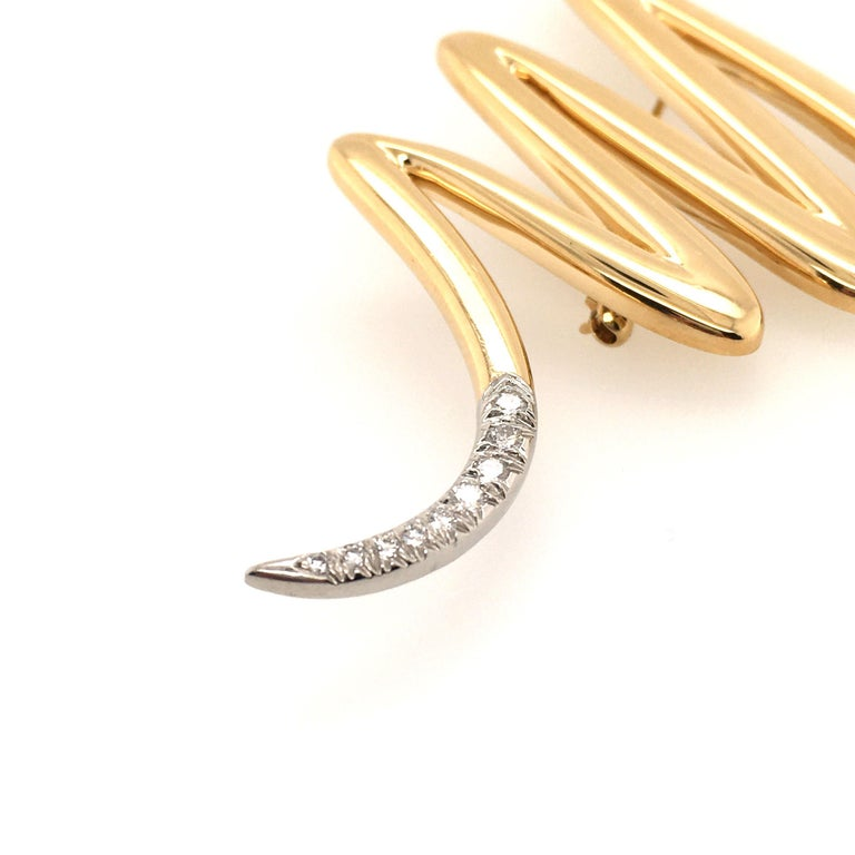 An 18 karat yellow gold and diamond brooch. Paloma Picasso for Tiffany & Co. Circa 1980. Of squiggle design, enhanced by pave diamonds.