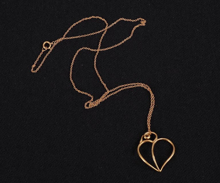 Paloma Picasso designed a  striking 18K gold heart pendant suspended from  a complementary gold chain for Tiffany & Co. in 1980. The heart is signed Paloma Picasso, 18K, 1980, and Tiffany & Co. on the back. It is in excellent condition and comes