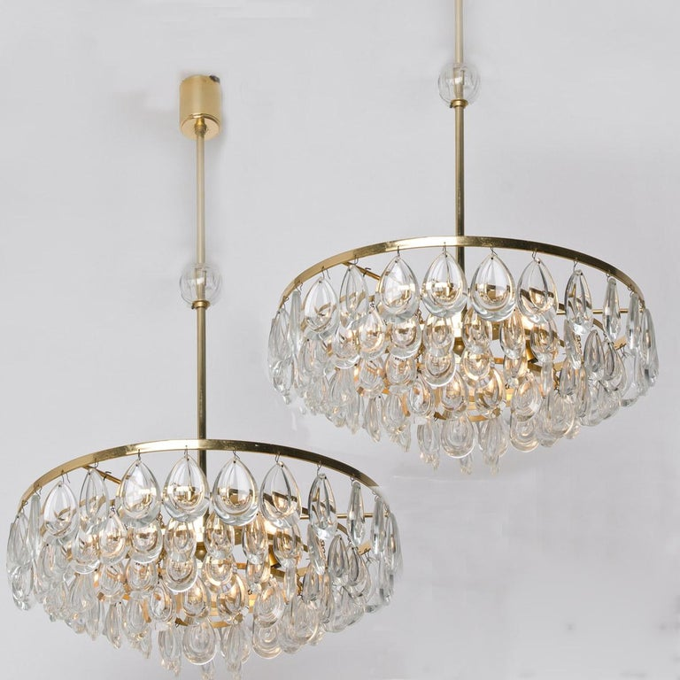 Wonderful pair of gilded brass and faceted crystal chandeliers by Palwa, Germany, manufactured in midcentury. Minimalistic design executed with a taste for excellence in craftsmanship. The Glass bulb on the rod can be removed if