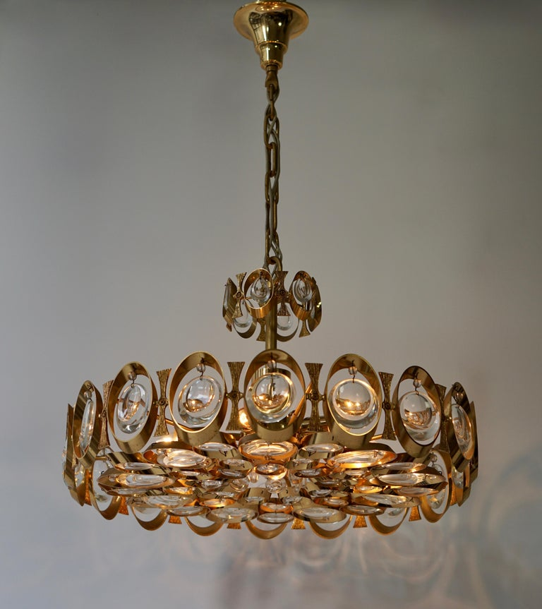 A stunning 24-karat gold-plated brass Hollywood Regency chandelier or pendant light by Palwa (Palme & Walter), Germany, manufactured in midcentury, circa 1970 (end of 1960s or early 1970s). This wonderful fixture is made of a gilded brass frame
