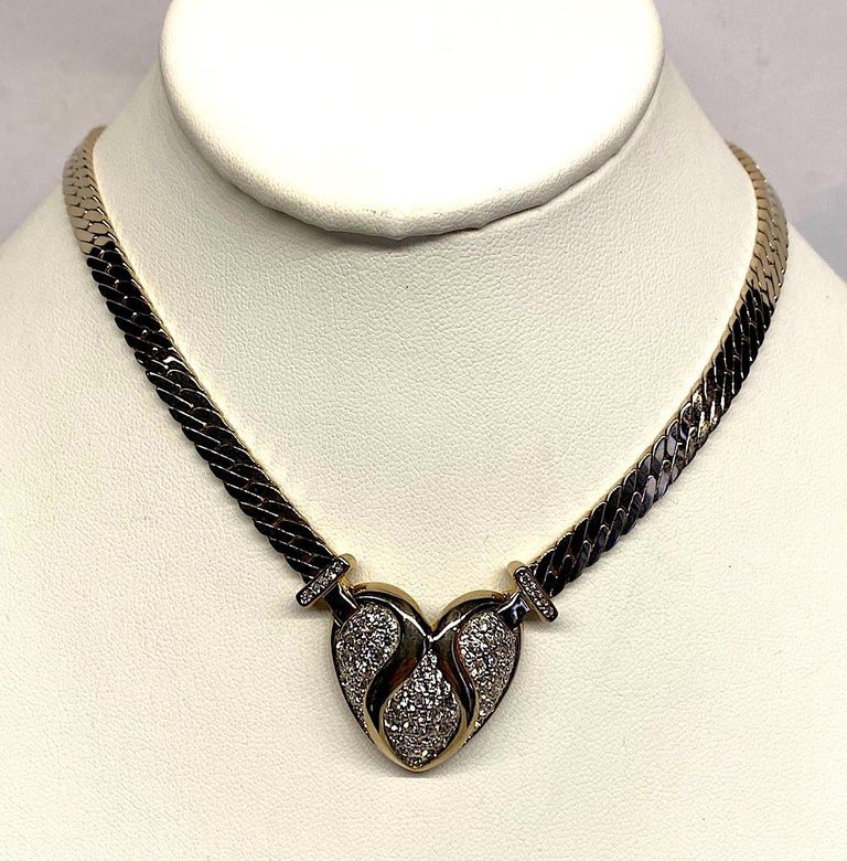 A lovely vintage heart pendant necklace by quality jewelry company Panetta circa 1980. The necklace is comprised of two gold plate flat curb link strands that meet in the center at a pave' rhinestone set heart. The heart is 1 inch wide and high in