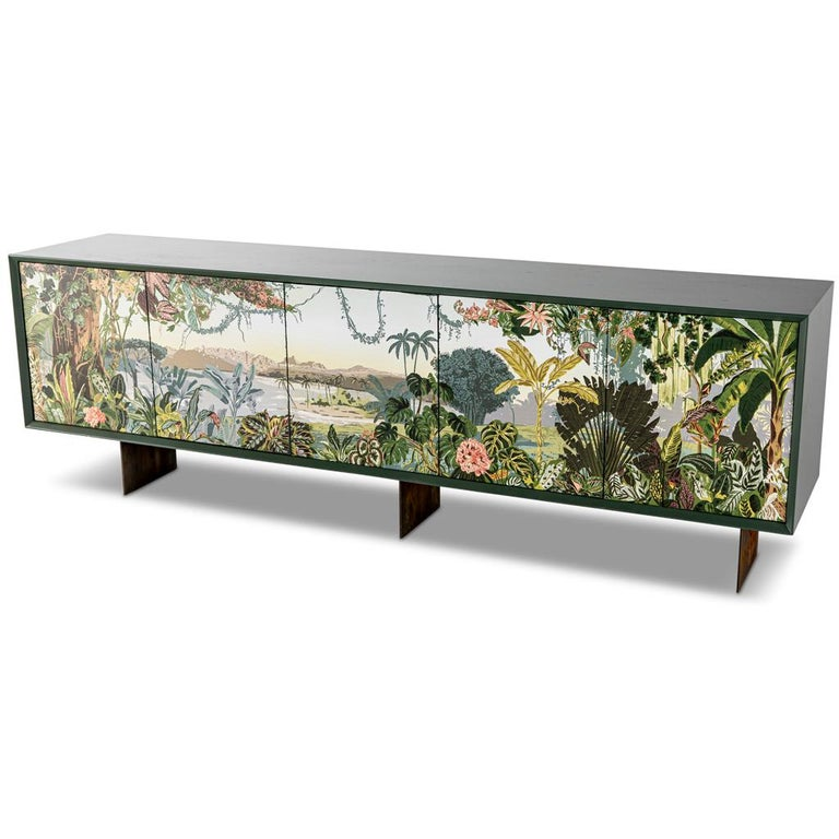 This modern sideboard server has a panoramic Trompe L'Oeil design on the doors, the panoramic Trompe L'Oeil shows a tropical vista of floral, shrubs, tress & vines with a mountain range in the far background. This unique sideboard has a timber