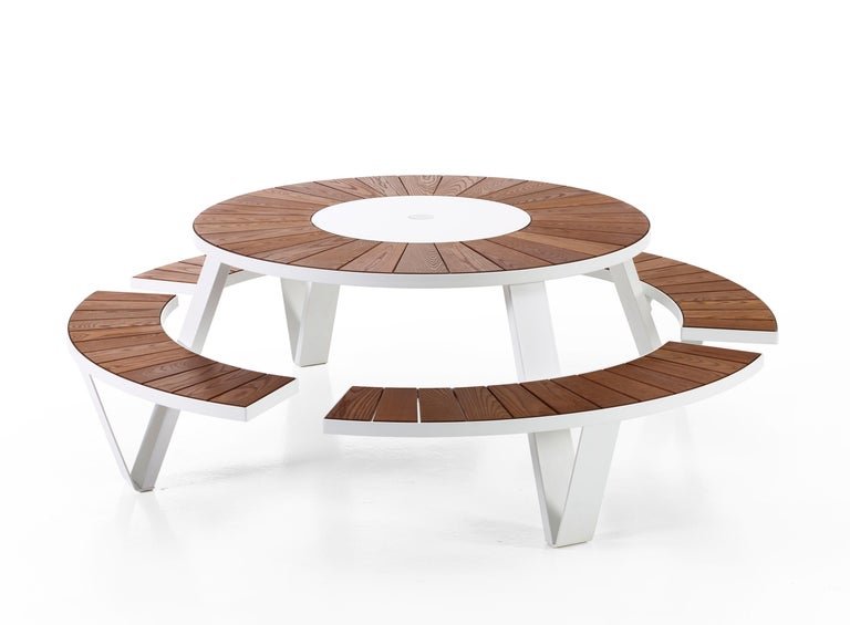The Pantagruel round picnic table seats eight people comfortably and includes a Lazy Susan. The frame comes powder coated as well as galvanized, tabletop and seats comes in natural Iroko hardwood. Includes Inumbra Parasol that connects to the
