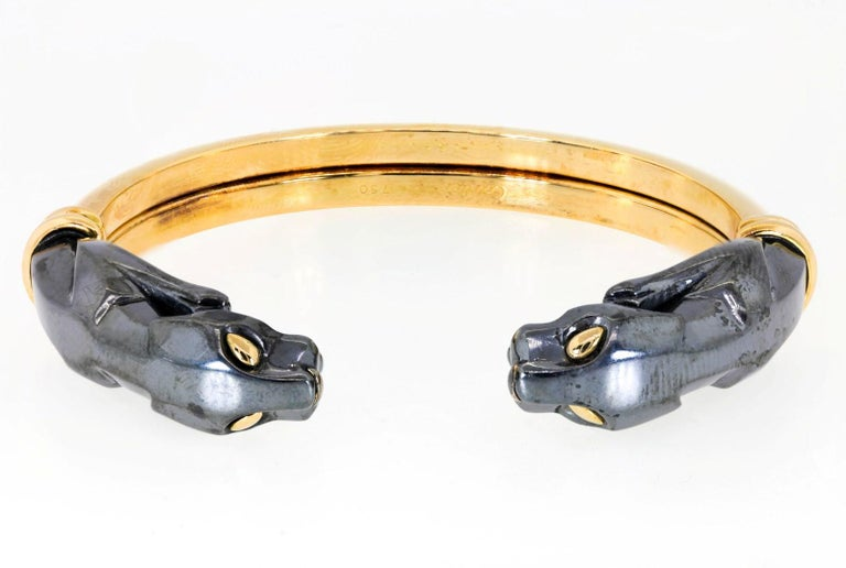 Cartier exquisitely crafted this scarce bangle in 18KT yellow gold and Hematite.  It features the iconic Cartier pouncing Panthers replete with golden eyes.  The gold section of the bangle flexes allowing easy wear and removal on a medium size