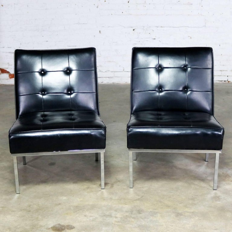 Awesome pair of Mid-Century Modern or MCM slipper chairs in black faux leather or Naugahyde by Paoli Chair Co. done in the style of Florence Knoll. Original tag on one chair dated 1968. They are in good original condition. There are a few repaired