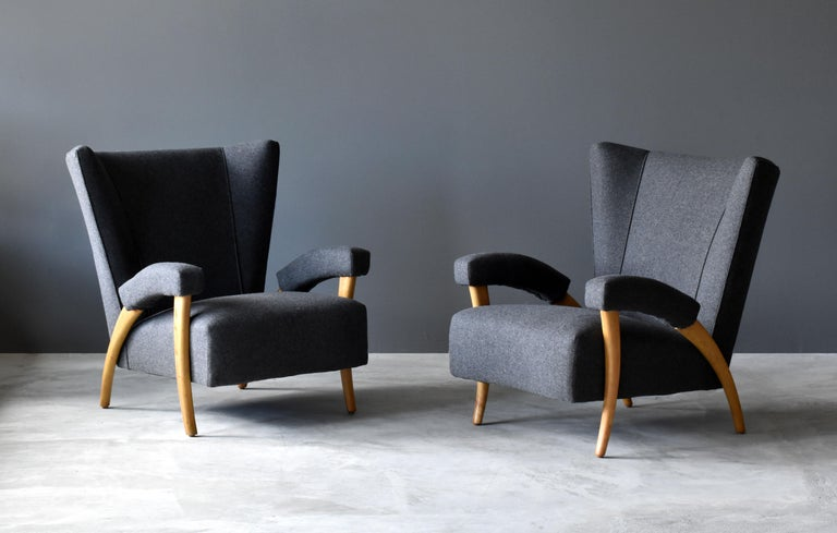 A pair of early and organic modernist lounge chairs or armchairs. Design attributed to Paolo Buffa.  The brand new European high-end fabric contrasts the lightly restored light oak. Construction of chair includes spring seats and spring-padded