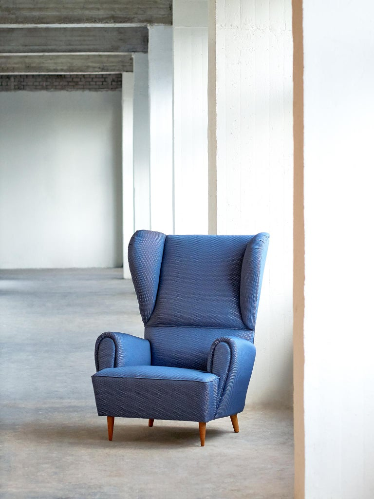 This generously sized wingback chair by Paolo Buffa has a grand yet playful design. Paolo Buffa is known for his modern interpretation of classical design, in which dimensions and proportions are transformed into refined and exciting new shapes. The