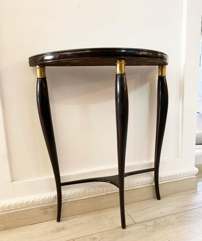 An elegant modern neoclassical console by Paolo Buffa with stunning hand carved wood legs in a stunning curved form and united by an angular 3 part stretcher, finished with brass decorations. Wonderful green glass top.