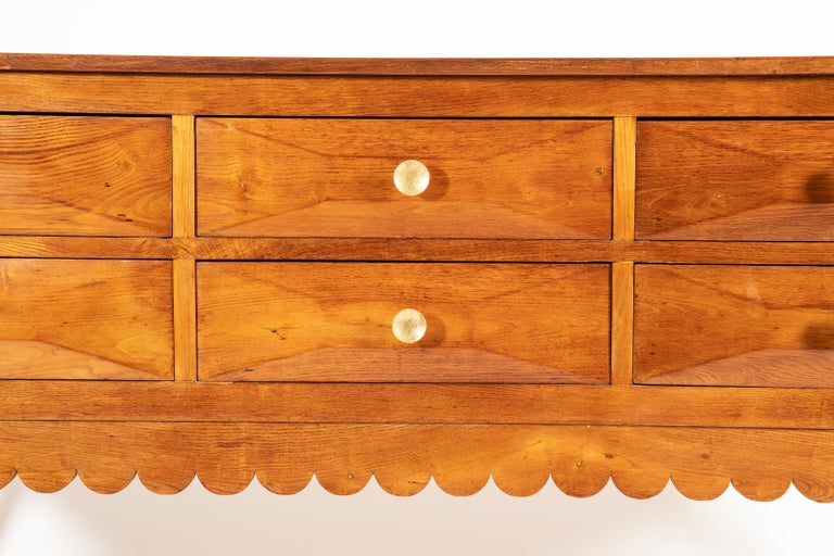 Extraordinary and rare solid oak credenza with scalloped edge details, featuring six rusticated ashlar-work drawers, for tapered legs ending in brass sabots and beautiful and original brass handlers. This credenza has been designed by Paolo Buffa in