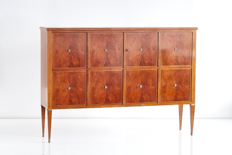 This large four-door panelled cabinet was designed by Paolo Buffa in the early 1950s. The composition of the striking grain of the eight mahogany veneered panels and the decorative brass details give the cabinet a refined and elegant appearance. The