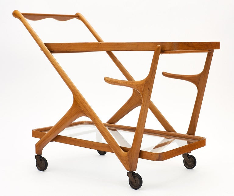 Italian bar cart in the manner of Paolo Buffa. This piece is made of solid, high-quality birch wood with a dynamic modernist structure. There are two glass shelves, and the cart rolls on original working casters. We love the small tray and