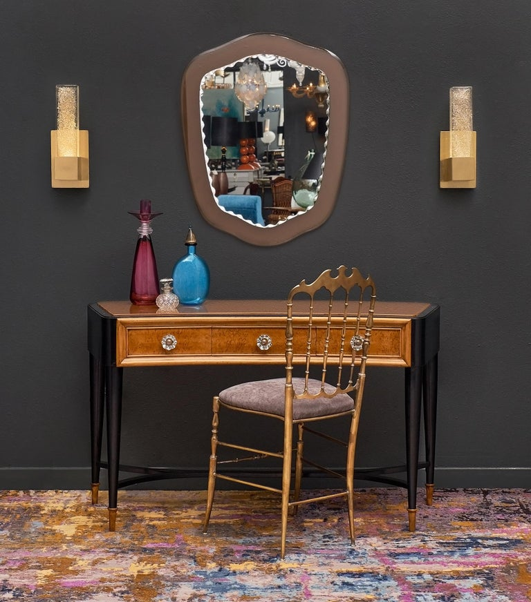 Italian console or vanity in the manner of Paolo Buffa with an elegant, curved shape. This piece features a tinted glass top original to the piece and three dovetailed drawers with original hardware. The tapered legs are connected with an