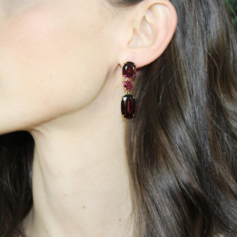 One-of-a-kind oval and trillion-shaped three stone rhodolite garnet earrings set in 18 karat rose gold with pave-set round, brilliant diamonds.  The weight of each earring will not pull down the ear and is designed specifically for maximum comfort.