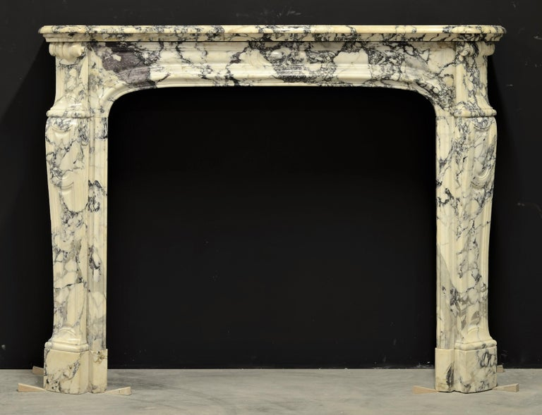 Superb French Pompadour style Louis XV fireplace mantel executed in beautiful Paonazetto marble. The soft toned marble combined with the hard veins makes this a true jaw-dropper. Great usable dimensions.  Perfect original conditions, brass side