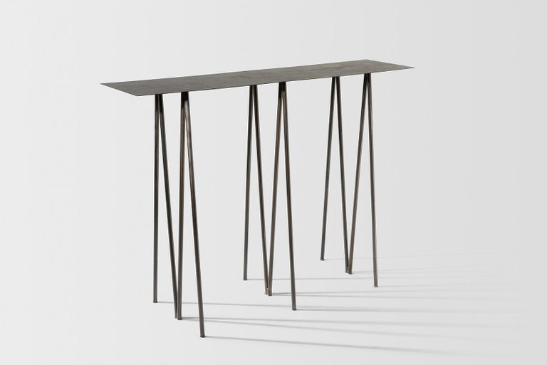 Where metal implies sturdiness, and calls for strong industrial motifs - the I/ the H, the beam / the cross, the Paper Table is a play on our own sense of balance.   It questions the thinness of both surface and structure, in order to reach their